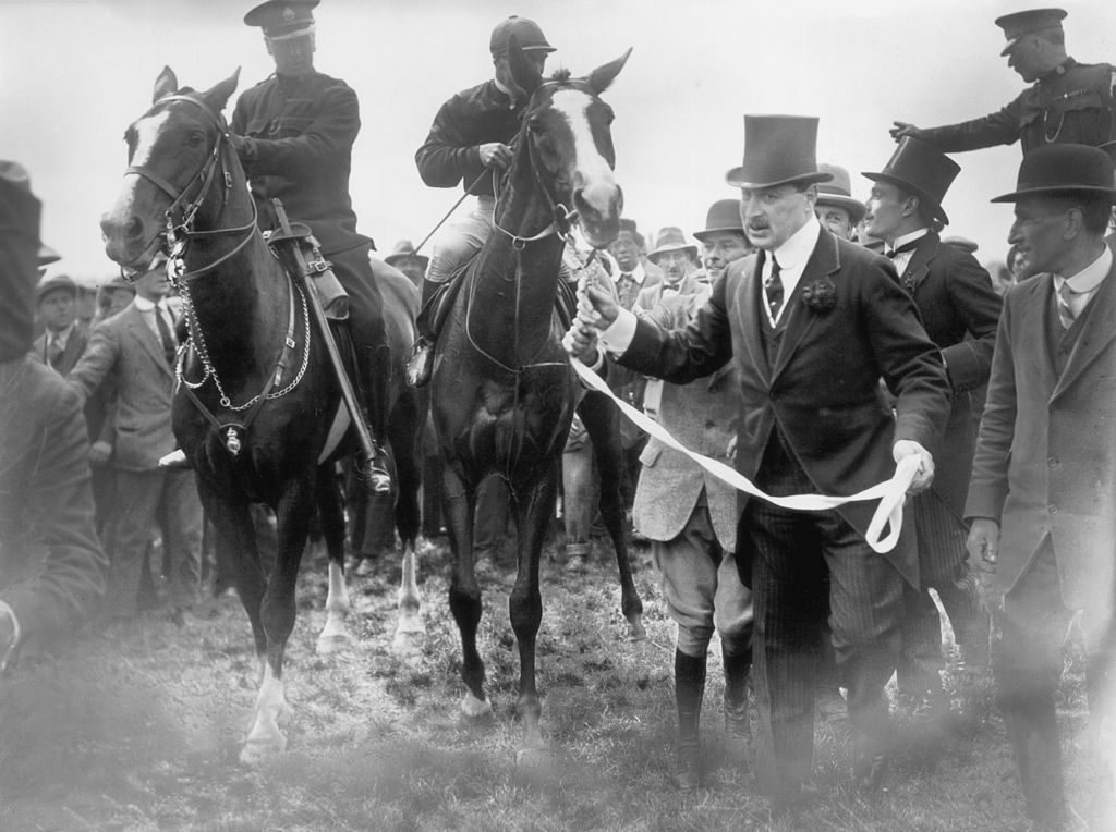 black and white photo showing a horse being led to a race
