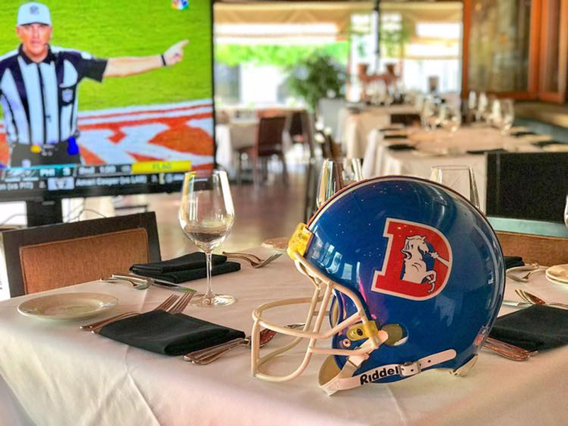 Elway's photo of helmet on table with TV on in the background located in Colorado