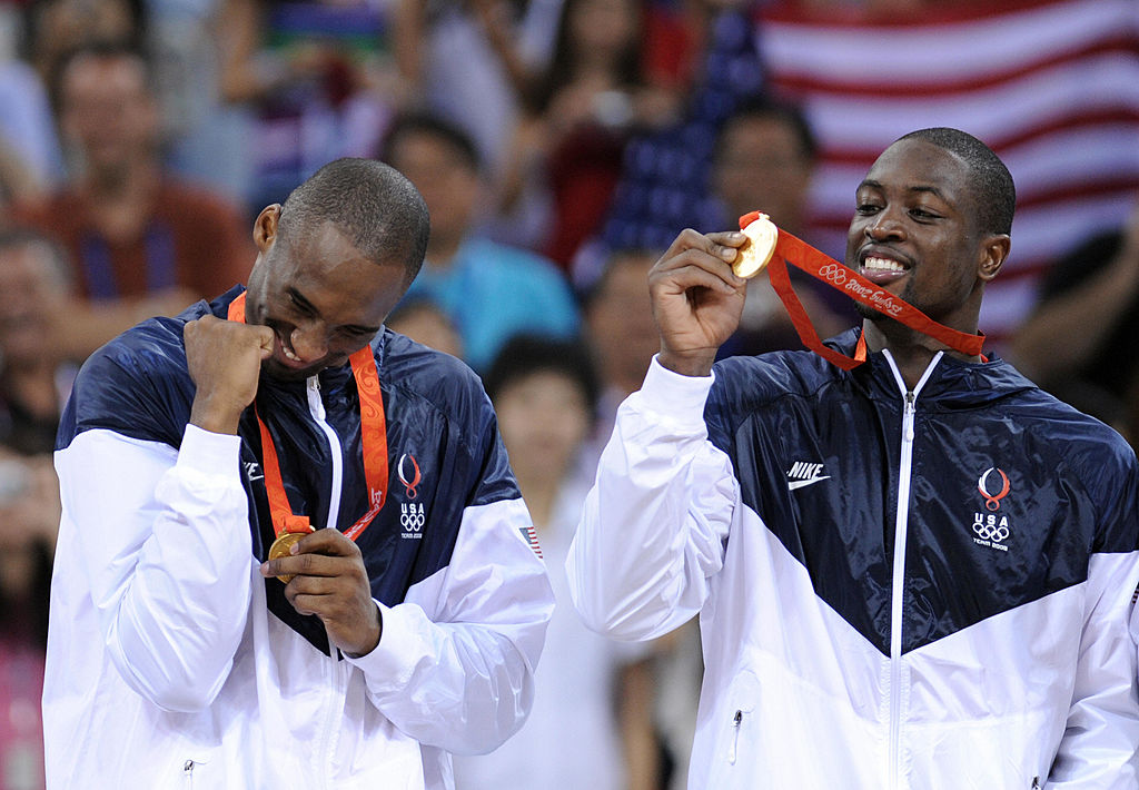 USA's Kobe Bryant and USA's Dwyane Wade bite their medals on the podium after the men's basketball gold medal match