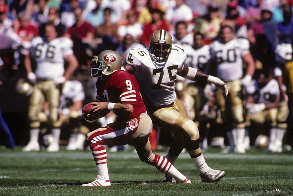 Bruce Clark closes in quarterback Jeff Kemp #9 of the San Francisco 49ers during the game at Candlestick Park