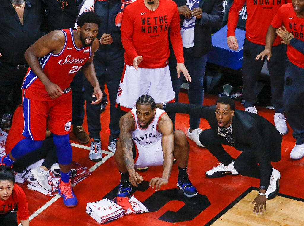 Philadelphia 76ers center Joel Embiid (21) watches from the corner as Toronto Raptors forward Kawhi Leonard (2) squats down and sticks out his tongue-1143370836 (1)