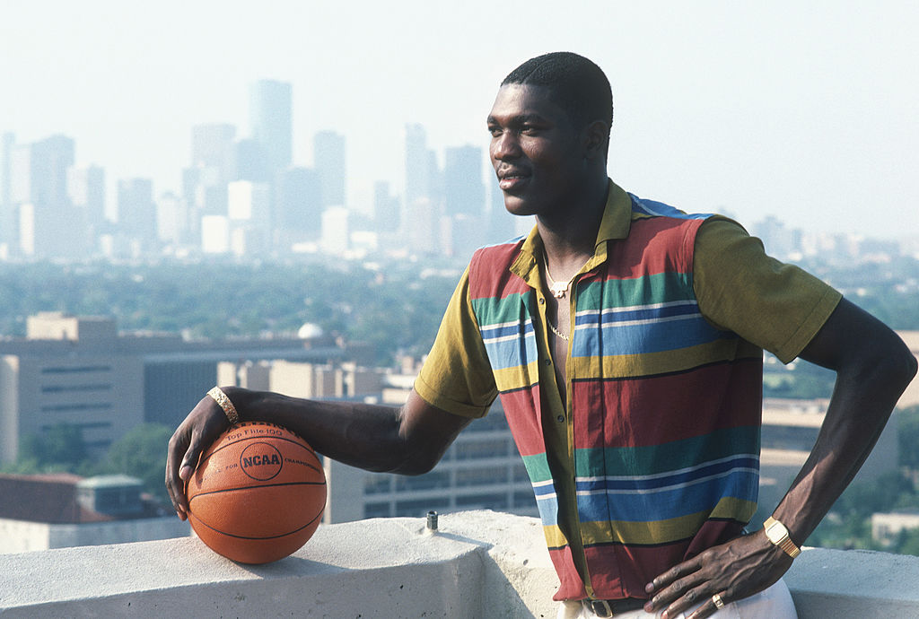 Hakeem Olajuwon #34 of the Houston Rockets poses in front of the Houston skyline for a photo-51763624