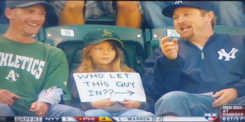 young oakland a's fan with a sign pointed at a yankees fan