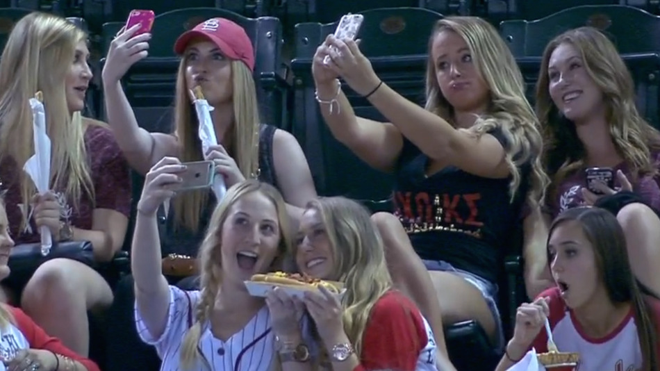 sorority girls taking selfies at baseball game