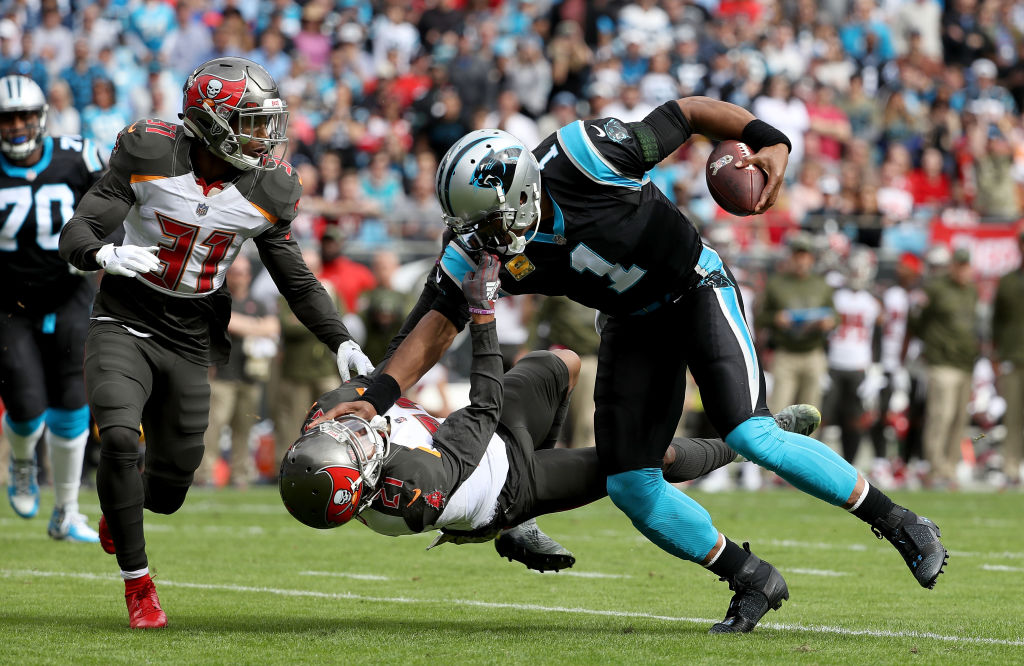 Cam Newton #1 of the Carolina Panthers runs the ball against Justin Evans