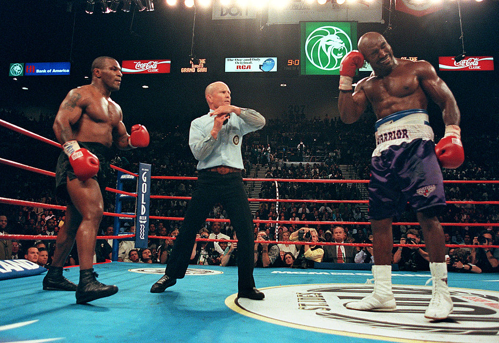 Evander Holyfield (R) holds his ear as Mike Tyson (L) watches
