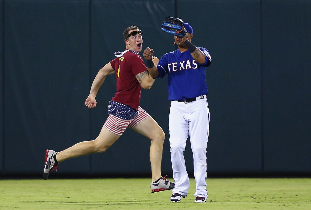 A fan runs across the field past Leonys Martin #2 of the Texas Rangers in the top of the eighth inning at Globe Life Park in Arlington on July 11, 2015 in Arlington, Texas.