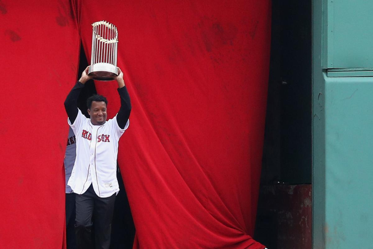 Pedro Martinez enters the field carrying the 2004 World Series Championship trophy