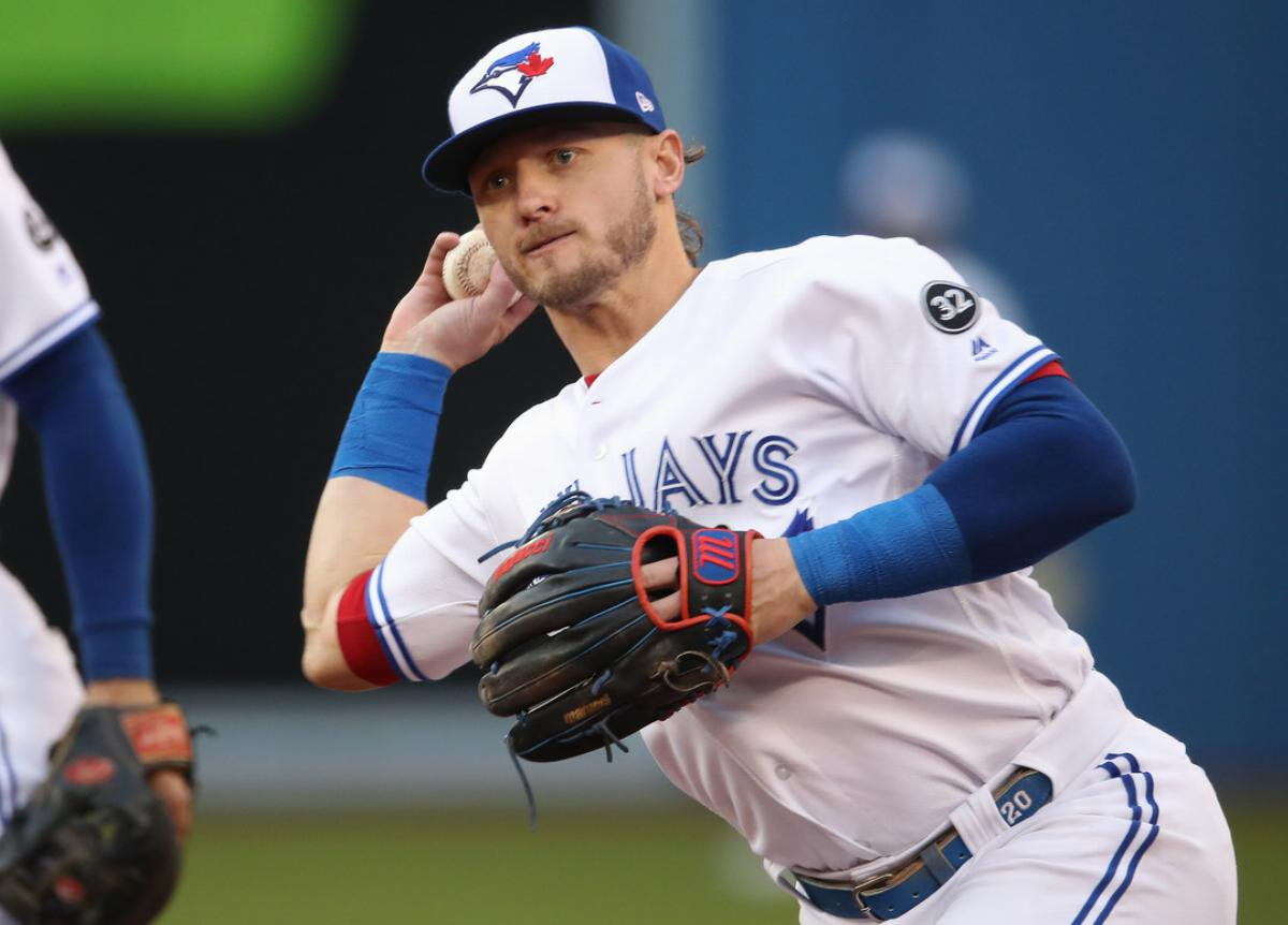 Josh Donaldson #20 of the Toronto Blue Jays makes the play and throws out the baserunner in the third inning during MLB game