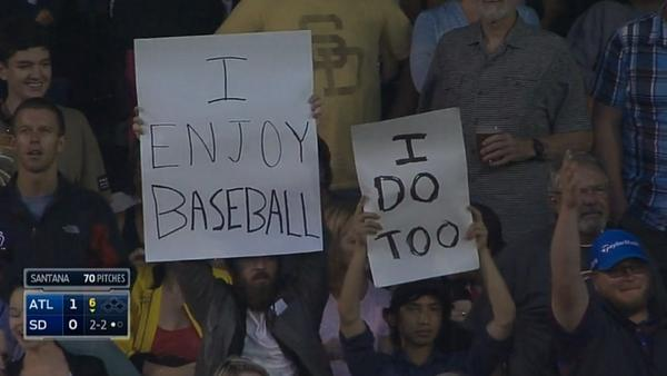 a fan holding a sign that reads i enjoy baseball