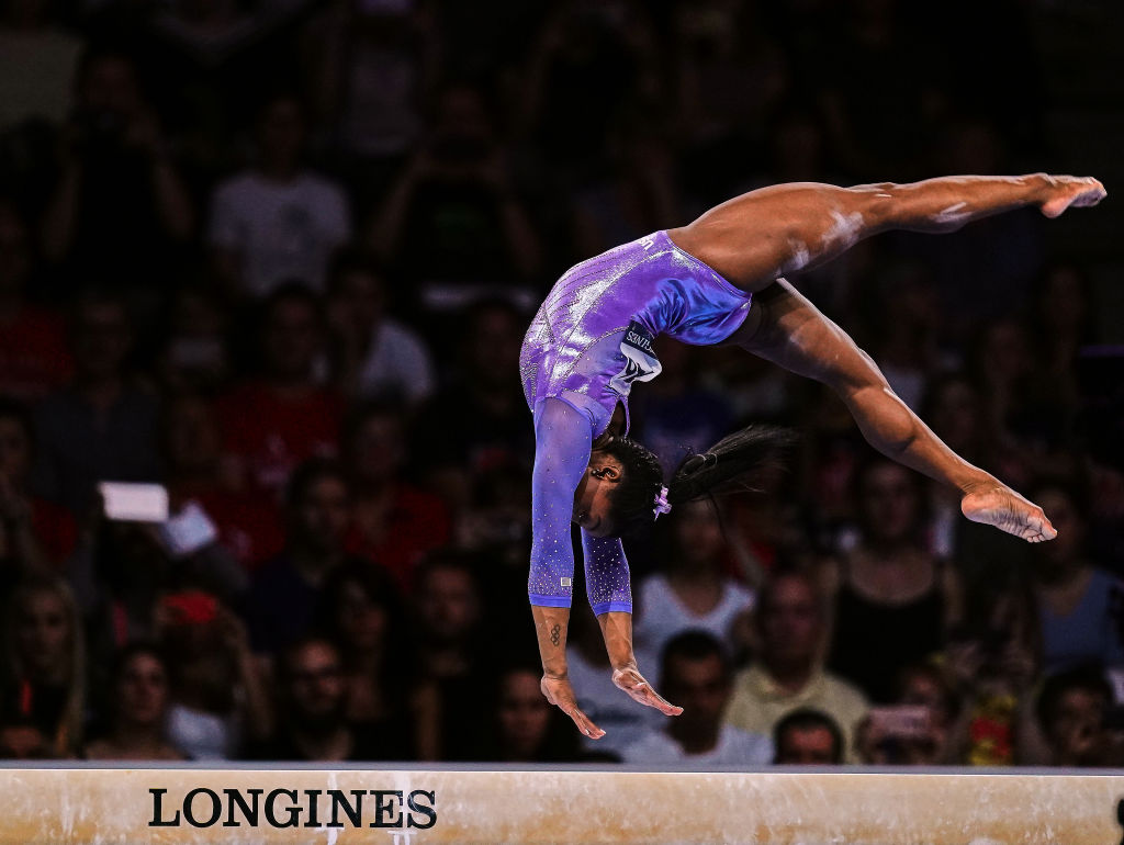 simone biles performing a balance beam routine