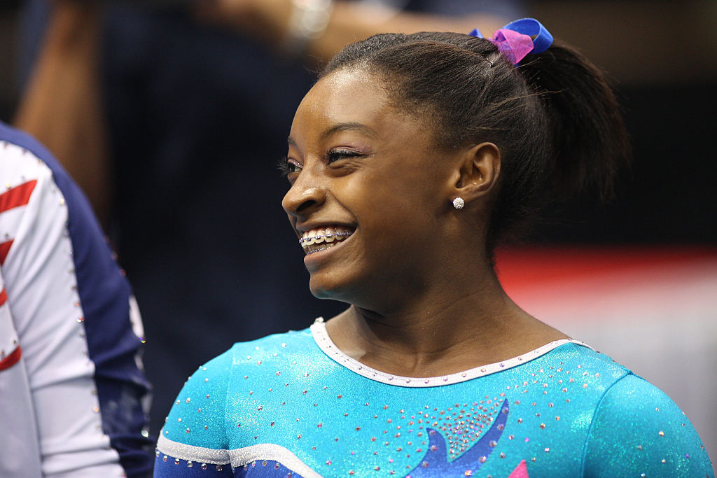 simone biles smiling after a routine