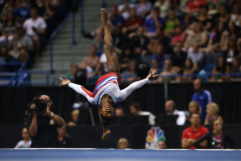 simone biles doing a flip on the mat