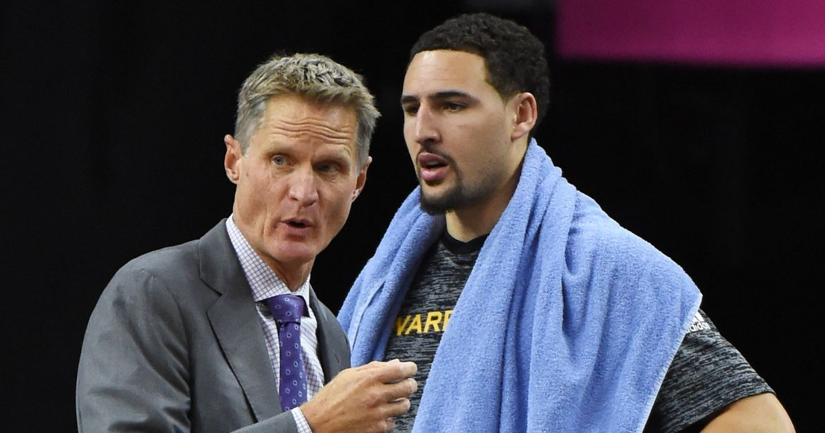 Coach Steve Kerr of the Golden State Warriors talks to Klay Thompson #11 on the bench