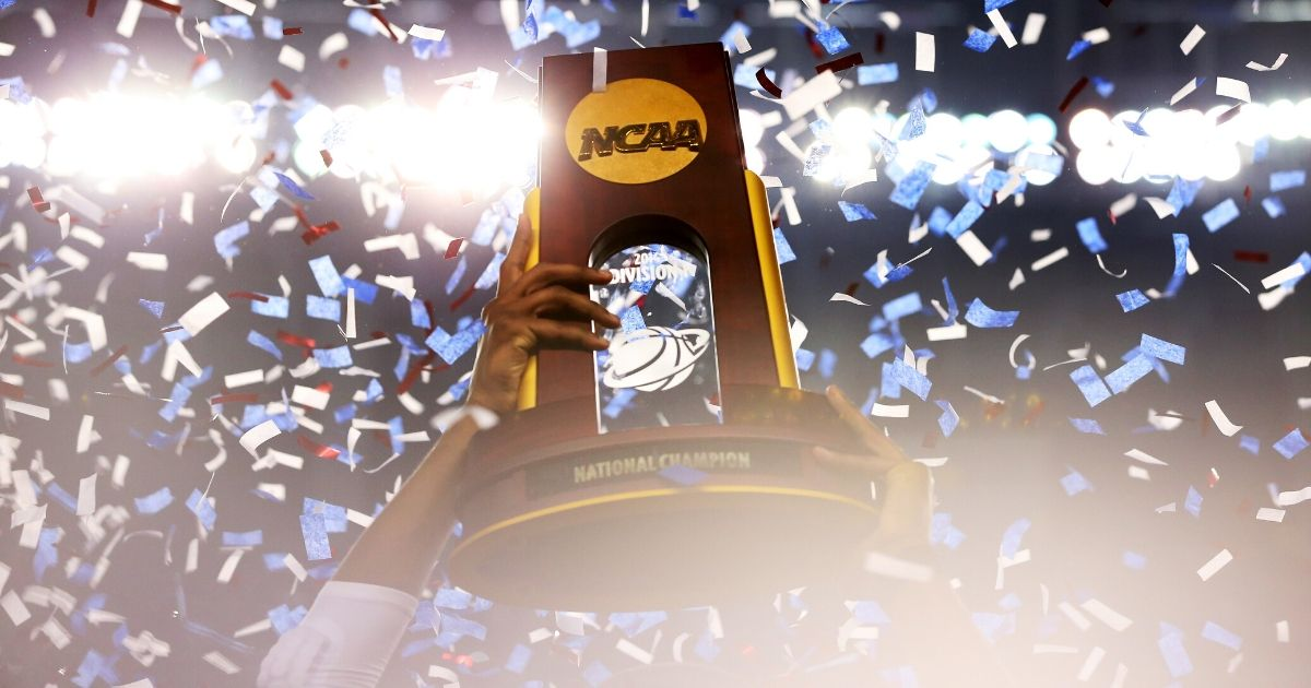 An NCAA trophy is held up in the air with confetti in celebration.