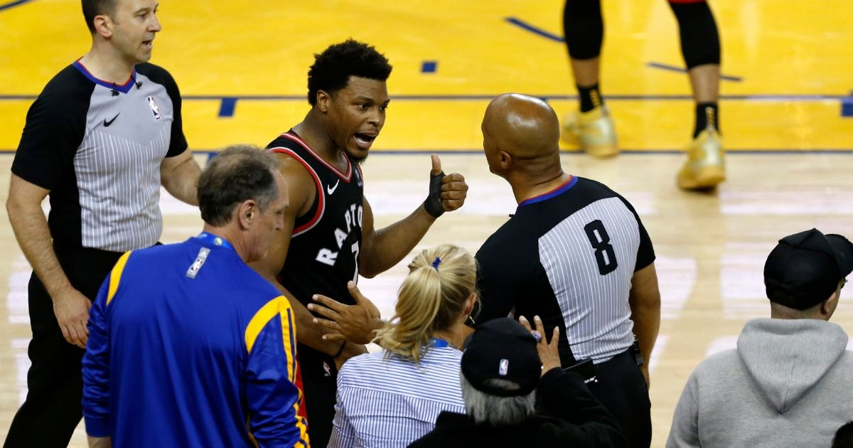 Kyle Lowry of the Toronto Raptors complains to referee Marc Davis after being pushed by Warriors minority investor Mark Steven