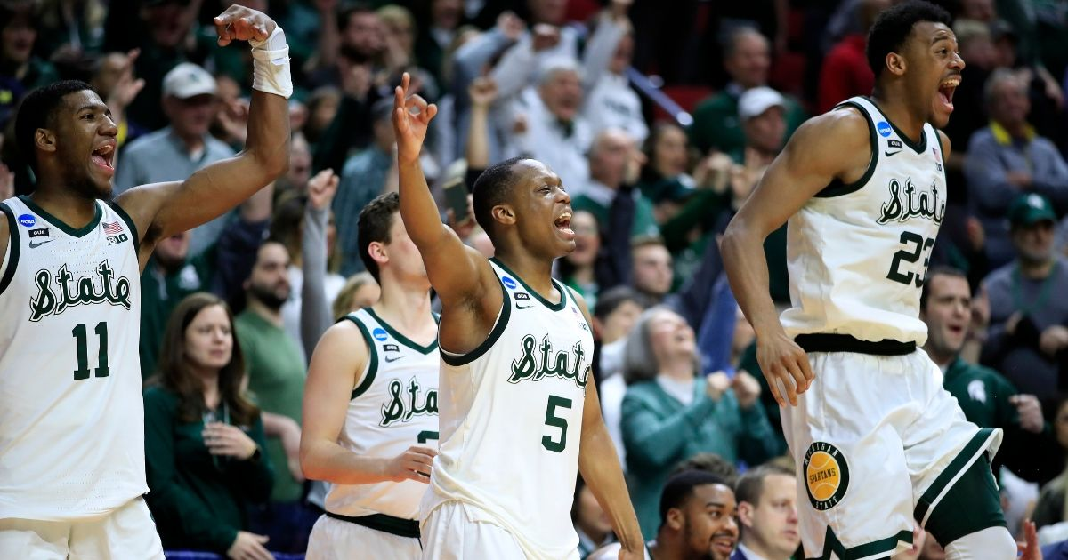 aron Henry #11, Cassius Winston #5 and Xavier Tillman #23 of the Michigan State Spartans celebrate from the bench