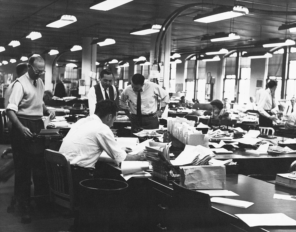 View of reporters and other workers at their desks in the city room or main news room of a newspaper