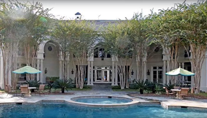 The mansion's backside overlooks a pool and jacuzzi.