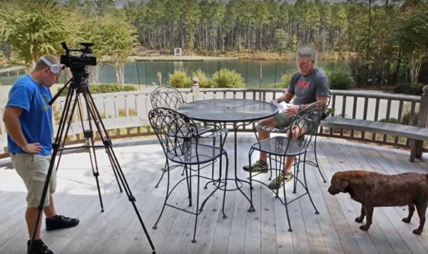 Brett sits at a table on his deck that overlooks a lake.