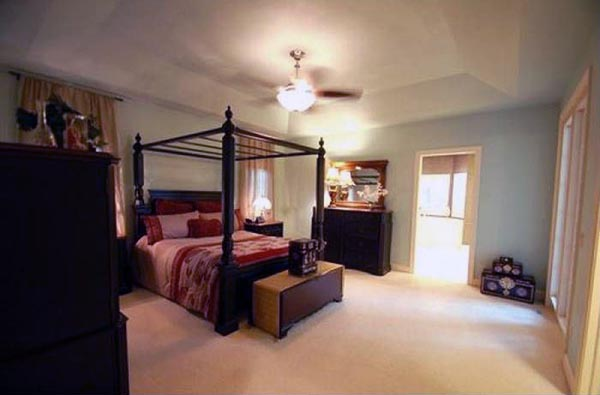 A spacious master bedroom is dressed with dark, wood furniture.