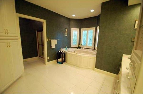 A spacious master bathroom features a large tub.