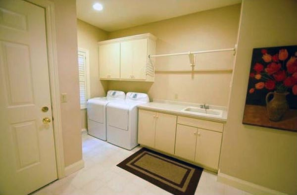 A laundry room features a sink, cabinets, and a side by side washer dryer.