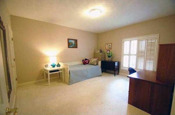 A spacious bedroom is furnished with a large desk and a twin bed.