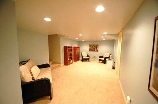 Stairs to the basement give way to a large seating area that acts as a foyer to the rest of the basement.