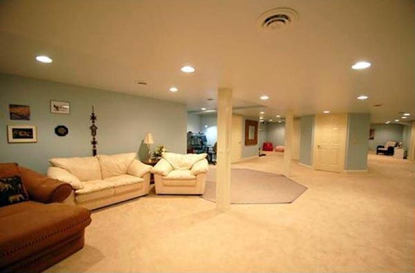 A large finished basement has carpeting and soft blue walls.