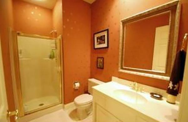 A modest bathroom is covered in dark peach colored wallpaper.