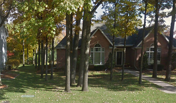 The front left of Brett's home is covered with autumn trees.