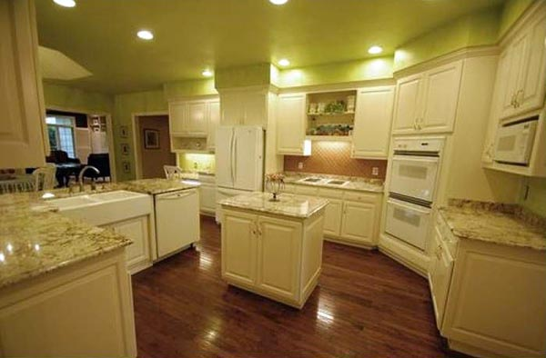 The kitchen features ample cabinetry surrounding a small island.