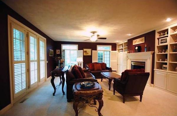 A sitting room has a large fireplace and floor to ceiling windows.