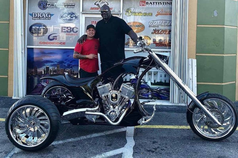 Shaq puts his arm around a mechanic while posing near his trike.