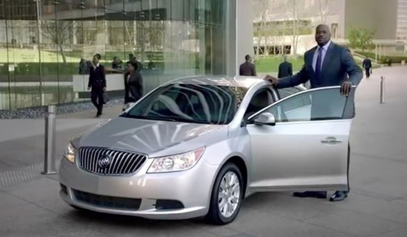 Shaq poses next to a Buick while filming a commercial.