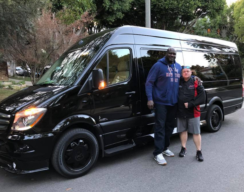 Shaq puts an arm around a mechanic in front of his Mercedes van.