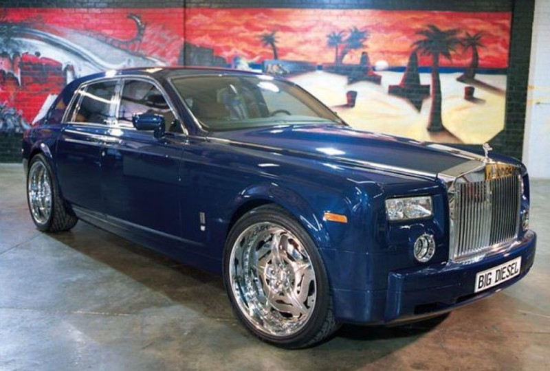 A blue Rolls Royce is parked in a garage.