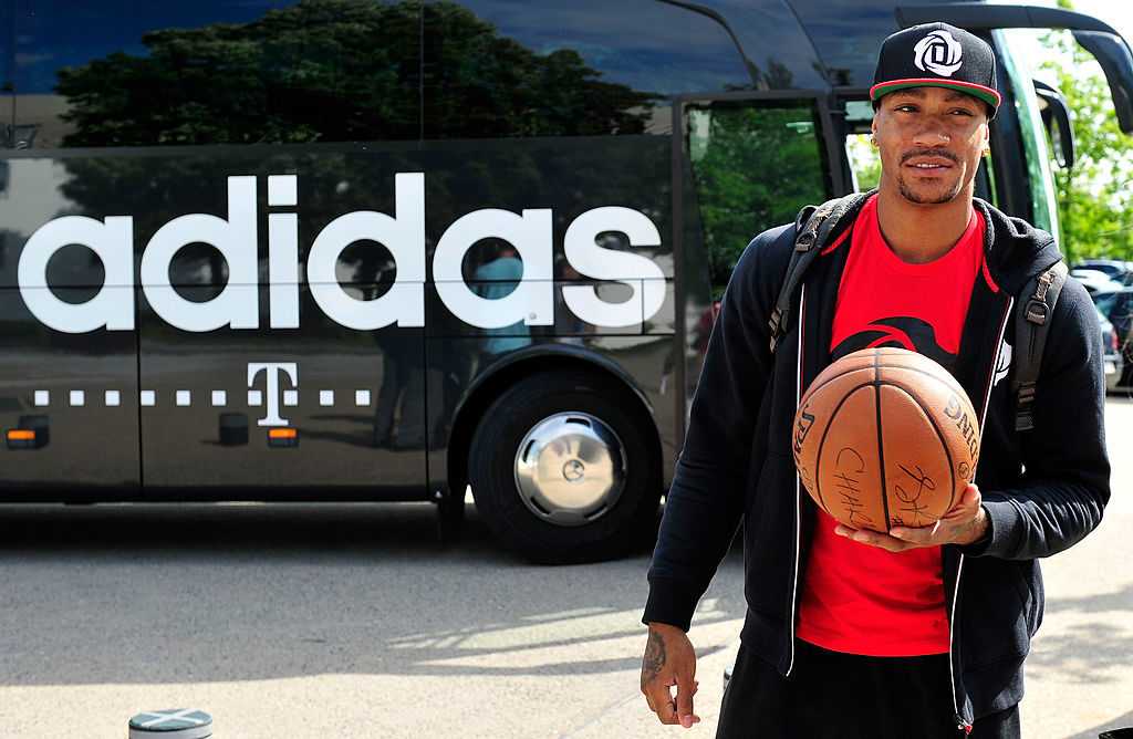derrick rose in front of an adidas bus