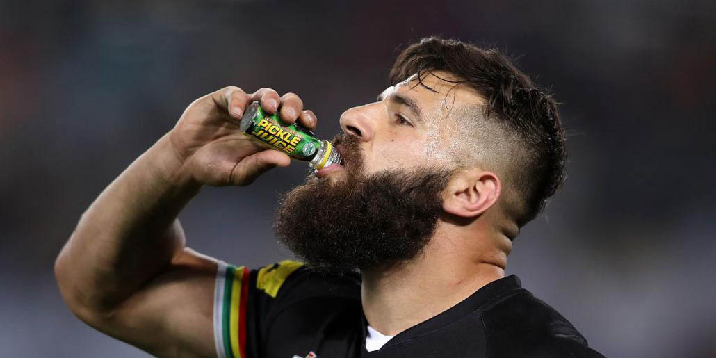 athlete drinking pickle juice to aid recovery