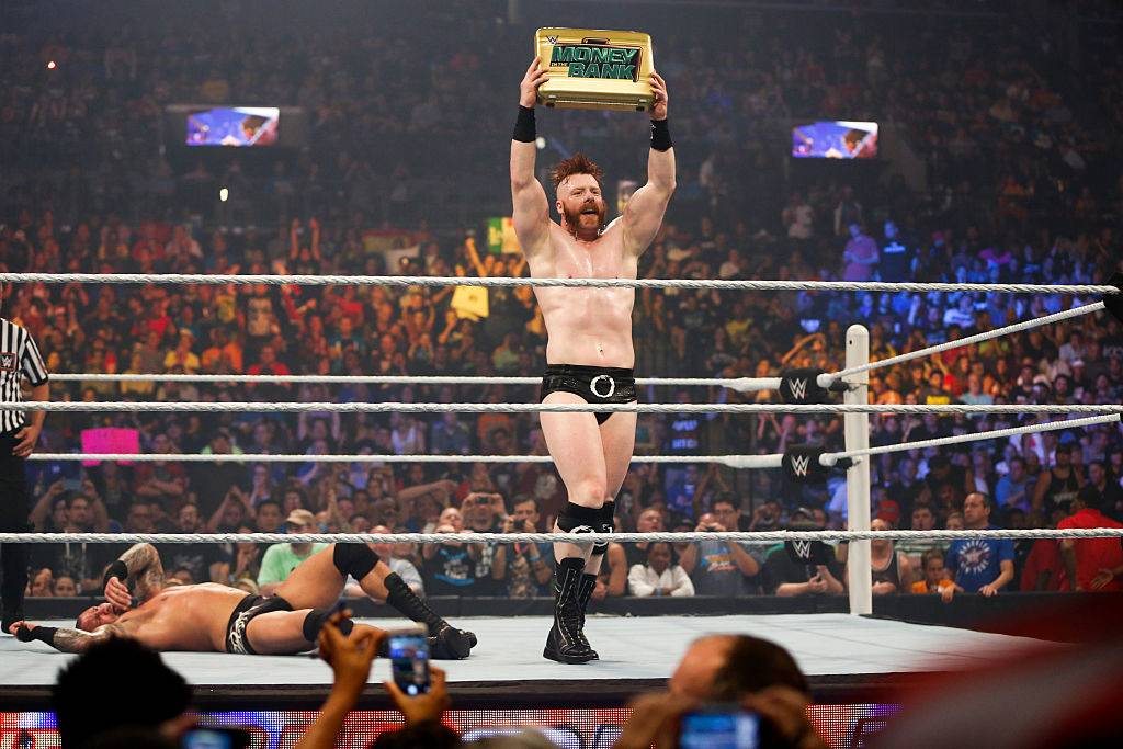 wrestler holding up the money in the bank briefcase
