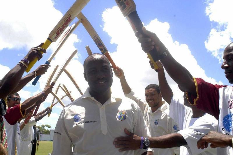Brian Lara walks under an arch of cricket bats.