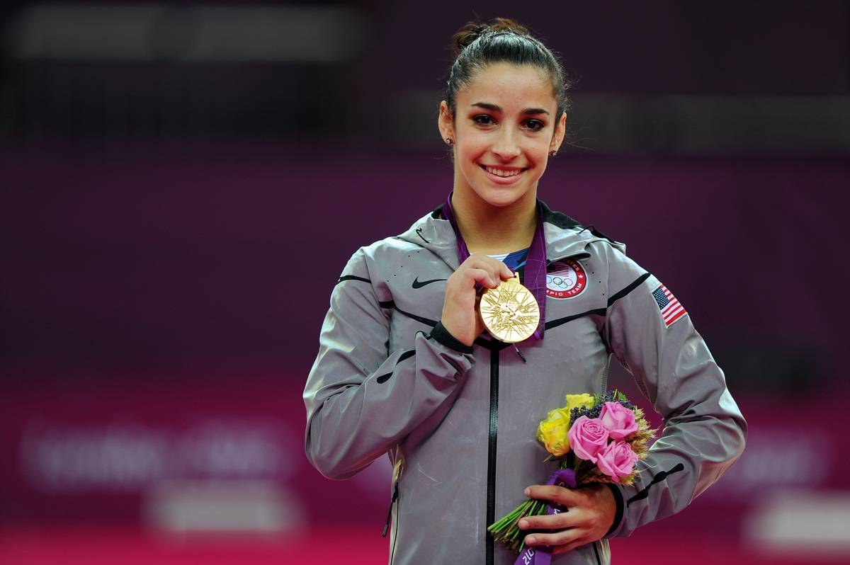 Aly Raisman holds up her gold medal after winning the 2012 Olympic Games.