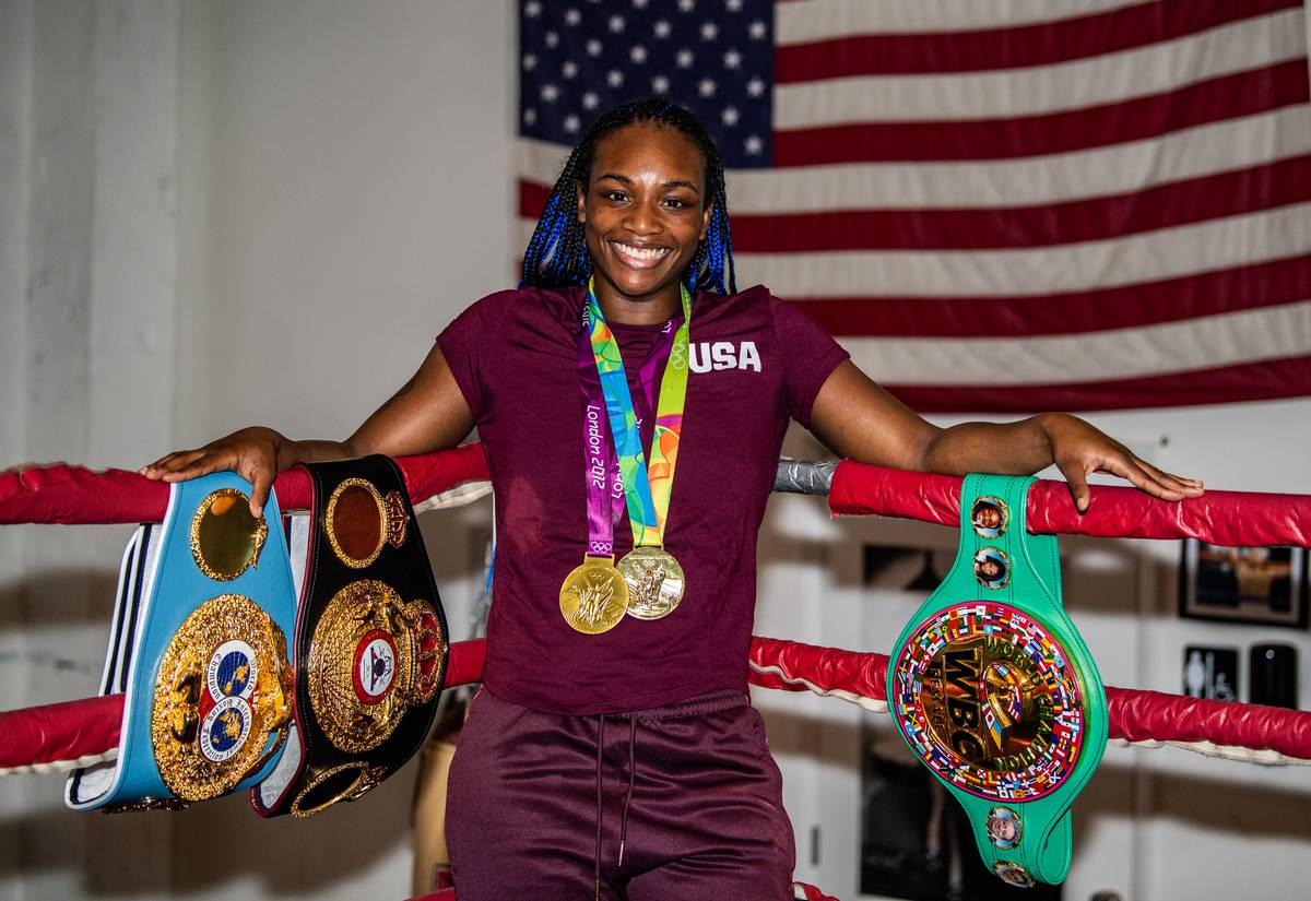Claressa Shields poses with all of her WBA and WBC medals in front of an American flag.