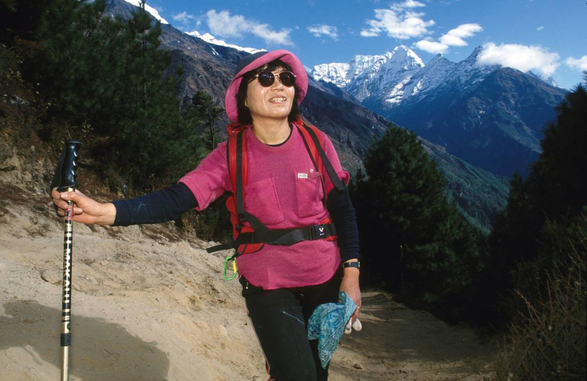 Junko Tabei poses in front of mountains.