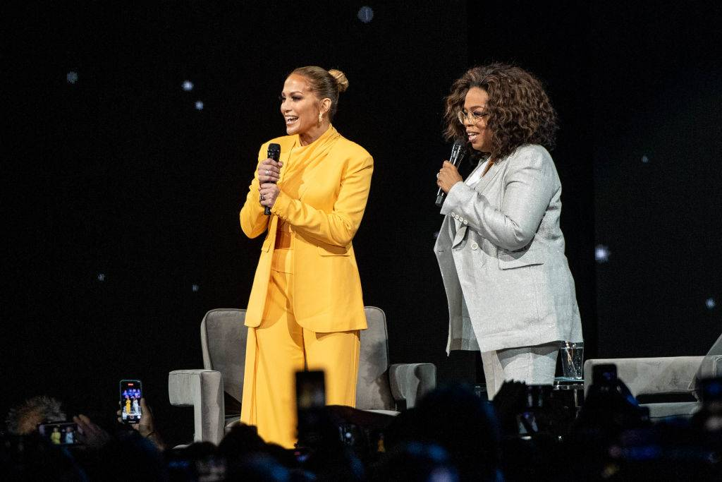 Oprah and Jennifer Lopez speak onstage in February 2020