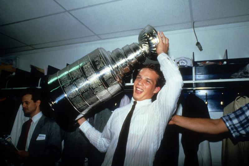 Kelly Buchberger holds the Stanley Cup in their Edmonton Oilers' locker room after defeating the Philadelphia Flyers.