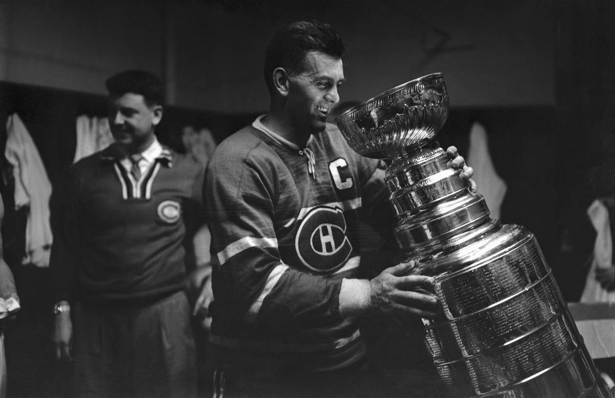 Maurice Richard tilts the Stanley Cup toward his mouth.