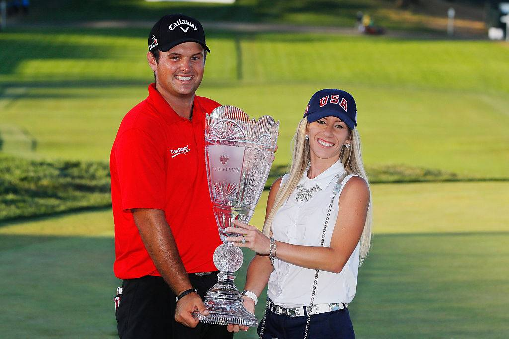 Patrick Reed poses with his wife Justine and the trophy after winning The Barclays