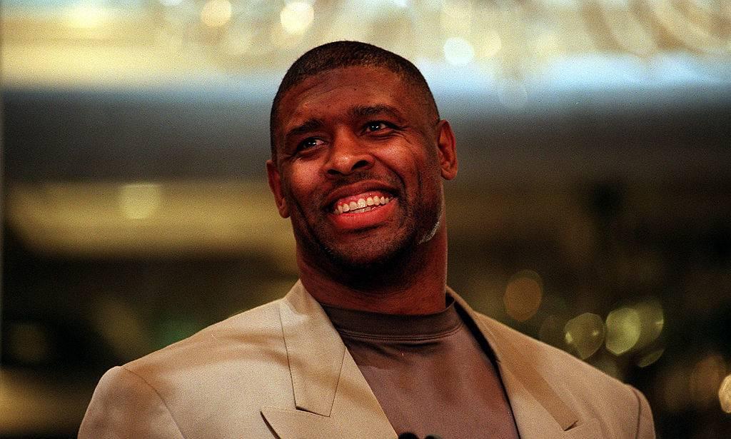 Reggie White smiling in suit